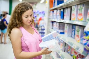 Young woman choosing washing powder in shop