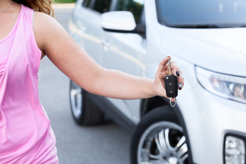 Unrecognizable woman showing ignition key in hand near own car