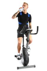 Trening na rowerze treningowym, mężczyzna pije wodę