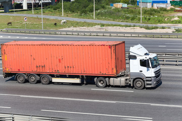 Semitrailer driving on highway with orange container