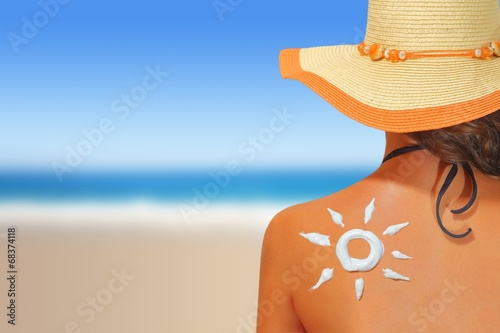 Woman with sun shaped sunscreen on her back - 68374118