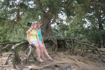 Mutter und Tochter sitzen auf riesiger Wurzel einer Kiefer