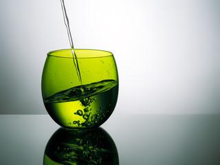 Beautiful green glass of water, pouring, splashing - unusual wat