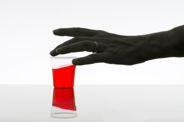 Woman reaching for red drink. Alcohol, addiction concept. Dark.
