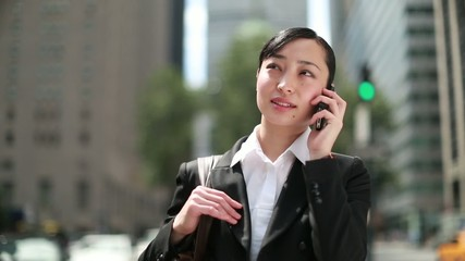 Young Asian business woman in city talking on cellphone