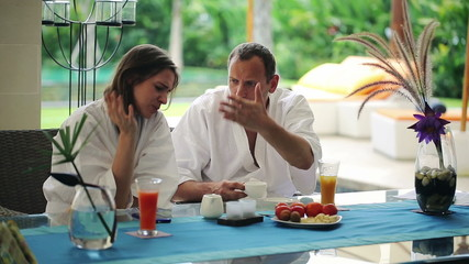 Young couple arguing by the table in luxury villa