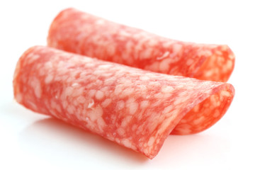 Thin slices of salami rolled into shape on white background.