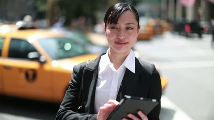 Young Asian business woman in city using tablet pc