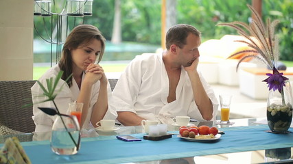 Offended couple sitting by the table in luxury villa