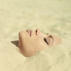 Beautiful lady buried in the sand