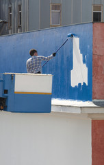 Worker coloring the wall