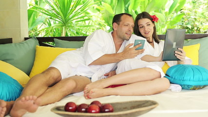 Couple with smartphone and tablet relaxing on gazebo bed
