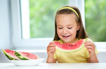 Cute little girl is eating watermelon