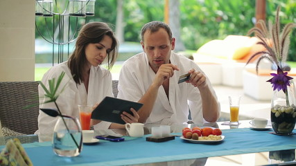 Couple online shopping on tablet computer by table