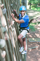 Climber in climbing wall at high rope course