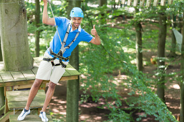 Man poses on platform at high rope course