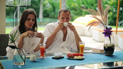 Couple talking during morning coffee by table in luxury villa