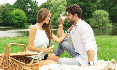 Young couple in love having picnic and drinking white wine