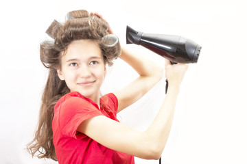 hairdryer in the hands of the girl in hair curlers