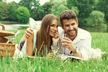 Happy couple on picnic drinking white wine