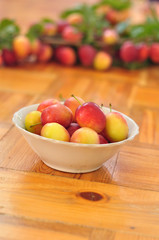 Plate of plums stands on wooden floor on blurred background