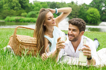 Attractive couple on picnic drinking white wine