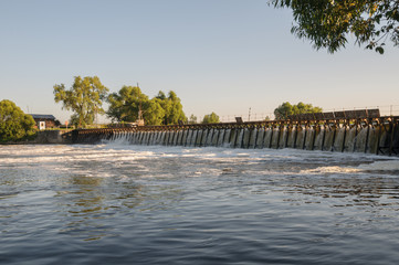 River dam in the summer backlit evening sun