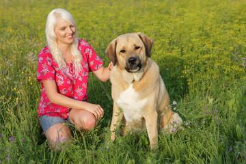 Hübsche Frau mit Hund in der Wiese