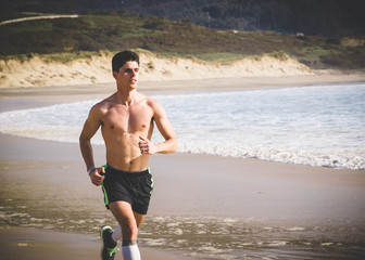 Young Man shirtless Running Along Beach