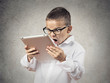 Shocked, frustrated boy using pad computer, grey background