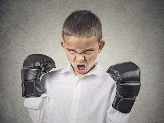 Angry boy wearing boxing gloves, ready to fight, grey background