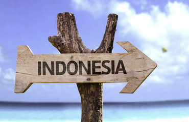 Indonesia wooden sign with a beach on background