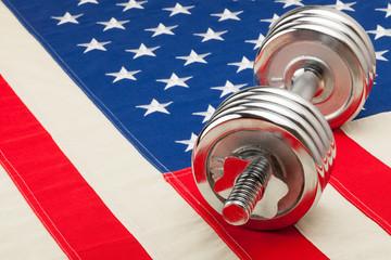 Metal dumbbells over USA flag as symbol of healthy nation