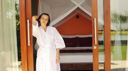 Happy beautiful woman in bathrobe standing in bedroom