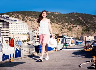 Young beautiful girl walking along the waterfront yacht club