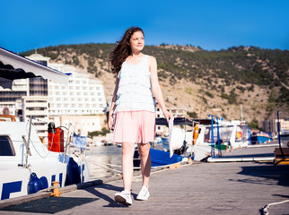 Young beautiful girl walking along the waterfront yacht club