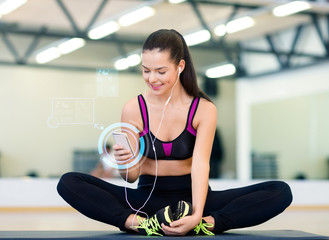 smiling woman with smartphone and earphones in gym