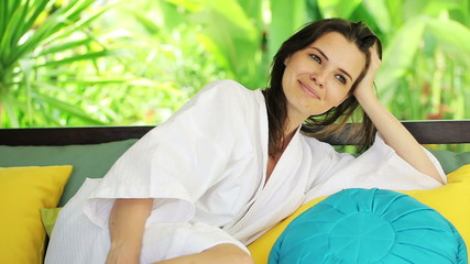 Beautiful woman relaxing on gazebo bed in garden