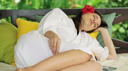 Beautiful woman in bathrobe sleeping on gazebo bed in garden