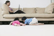 Mother working on laptop while children look under couch