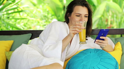 Beautiful woman with smartphone relaxing on gazebo bed in garden