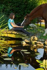 Frau mit Pferd am Teich