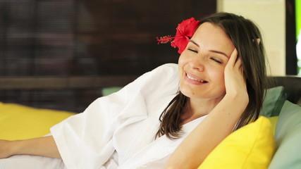 Beautiful happy woman relaxing on gazebo bed in garden