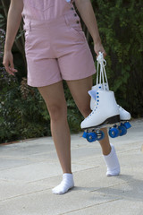 Teenage roller skater carrying her quad skates
