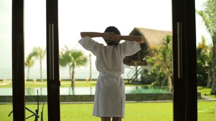Woman in bathrobe stretching on patio in luxury villa