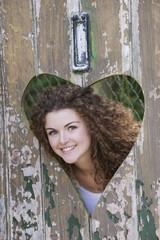 Teenager looking through heart shape in an old door