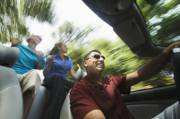 Man and women driving in convertible