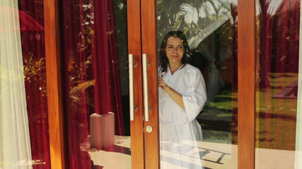 Woman unveill curtains, walking ot from bedroom in the morning