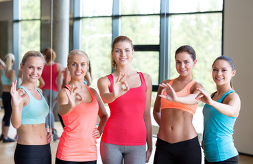 group of women showing ok sign in gym