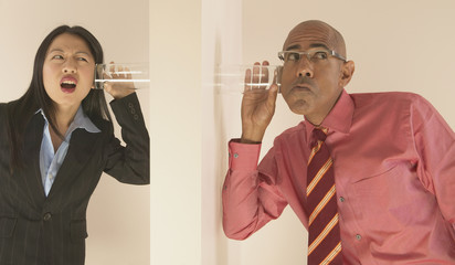Business people listening through wall with glass to ear